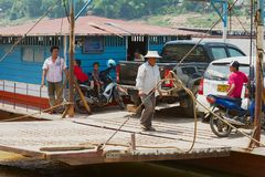 People embark cars and motorbikes to a local ferry boat to cross Mekong river in Luang Prabang, Laos. LUANG PRABANG, LAOS - APRIL 12, 2012: Unidentified people stock photography