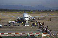 People embarking in an airplane. BARCELONA, SPAIN - July 28, 2014: Tourists ready to embark in a low cost airplane at the terminal of the airport of Barcelona stock photo