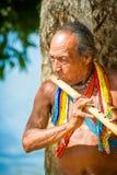 People in EMBERA VILLAGE, PANAMA. EMBERA VILLAGE, PANAMA, JANUARY 9, 2012: Unidentified native Indian man plays a flute in Panama, Jan 9, 2012. Indian Stock Photo