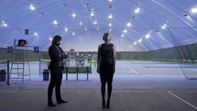 People emerges from dark. Woman and man stands in the dark. The lamps turns on around the people and illuminates the tennis court. Concept of the birth of new stock video footage