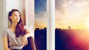 Sad pretty teenage girl sitting on windowsill Stock Photography