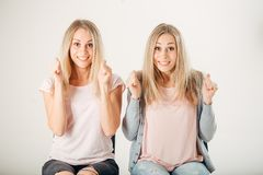 People, emotions and feelings. twin women having excited and winning looks. Two happy twin women having excited and winning looks, cheering, celebrating their Royalty Free Stock Photos
