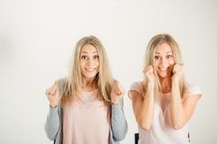 People, emotions and feelings. twin women having excited and winning looks. Two happy twin women having excited and winning looks, cheering, celebrating their Stock Photo