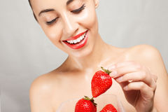 Sexy Woman Eating Strawberry. People, emotions, natural, food, beauty and lifestyle concept - Sexy Woman Eating Strawberry. Sensual Lips. Manicure and Lipstick Stock Image
