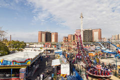 People enjoy the amusement area Luna park at Coney islandwalking along the promenade at Coney Island. New York, USA - OCT 25, 2015: people enjoy the amusement royalty free stock photography