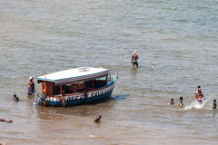 People enjoy the beach of Lake Malawi next to a boat. Stock Photography