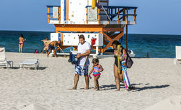 People enjoy the beach next to a lifeguard tower Stock Photography