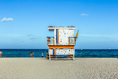 People enjoy the beach next to a lifeguard tower Royalty Free Stock Images