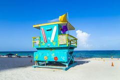 People enjoy the beach next to a lifeguard tower Stock Images