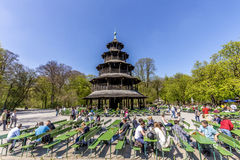 People enjoy the Biergarten near Chinese tower. MUNICH, GERMANY - APR 20, 2015: people enjoy the Biergarten near Chinese tower in English garden in Munich stock photography