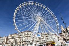 People enjoy big ferris wheel against a blue sky in Marseilles Stock Photo