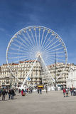 People enjoy big ferris wheel against a blue sky in Marseilles Royalty Free Stock Photography