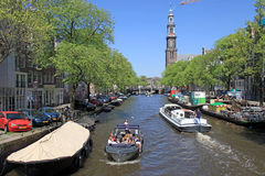 People enjoy a boat ride in the canals of Amsterdam. Royalty Free Stock Photo