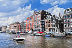 People enjoy a boat-tour in canal with ancient mansions, Amsterdam, netherlands Royalty Free Stock Images