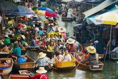 People enjoy boat tour at the floating market in Damnoen Saduak, Thailand. Stock Photo