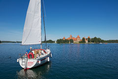 People enjoy boat trip at Galve lake with the Trakai castle at the background on a hot summer day in Trakai, Lithuania. Stock Photography