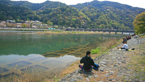 People enjoy of cherry blossom at Arashiyama. ARASHIYAMA-APR 17: Unidentified people have Hanami, enjoy of cherry blossom, party near Togetsukyo bridge on April royalty free stock photos