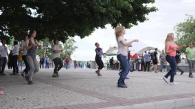People enjoy dancing on street, crowd repeat movements after dance teacher outdoors, stock video