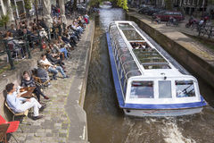 People enjoy drinks on embankment of amsterdam canal while touri Stock Photos