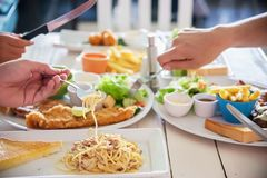 People enjoy eat spaghetti and steak together in a big meal set. Family happy time with food concept stock photography