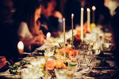 People enjoy a family dinner with candles. Big table served with food and beverages