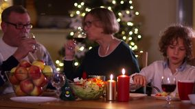 People enjoy a family dinner with candles. Big table served with food and beverages. Mature couple drinks red wine from