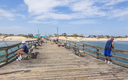 People enjoy fishing on old wooden fishing pier Royalty Free Stock Image
