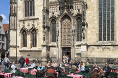 People enjoy food and drink on sidewalk cafe. Germany, North Rhine-Westphalia, city Münster: people, women and men, are consuming at the Lichtenmarkt in the royalty free stock photography