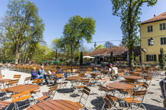 People enjoy the Hirschgarten near Chinese tower in English gar. MUNICH, GERMANY - APR 20, 2015: people enjoy the Hirschgarten near Chinese tower in English royalty free stock image