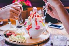 People enjoy mix fruit Bingsu on tray, Bingsu or Bingsoo. Korean shaved ice dessert with sweet toppings and fruits and varieties with ingredients stock image