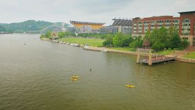 People Enjoy the North Shore in Downtown Pittsburgh. People in boats and kayaks enjoy the rivers in downtown Pittsburgh, Pennsylvania on a summer day. Heinz stock footage