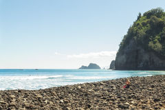 People enjoy ocean view and recreation. People enjoy the rocky beach after hiking into the Pololu Valley at the north end of the Big Island of Hawaii Stock Photography