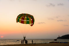 People enjoy parasailing at beach during sunset time Royalty Free Stock Photos