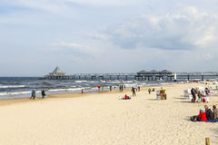People enjoy pier and beach. HERINGSDORF, GERMANY - APRIL 20, 2014: people enjoy pier and beach of Heringsdorf, Germany. The baltic Sea in Usedom Island is Stock Photos