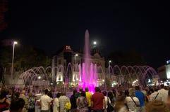 People enjoy pink illuminated fountain Royalty Free Stock Images