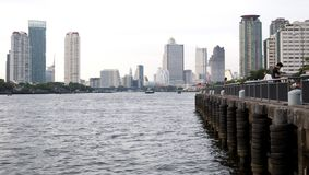 People enjoy a quiet time on a pier on the Chao Praya river in Bangkok, Thailand, with modern buildings in the background.  royalty free stock photography
