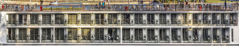 People enjoy river cruise ship with cabins on river Rhine. Royalty Free Stock Photos