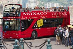 People enjoy sightseeing tour on the red Monaco city tour bus in Monaco. Stock Photo