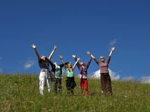 People enjoy the spring. Group people (mother with children - sisters, friends) with happy smiling facial standing in a green field, arms outstretched upwards royalty free stock photo