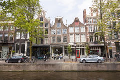 People enjoy spring sunshine in front of canal houses in amsterd Stock Image