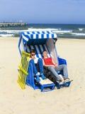 People enjoy sunbath in the roofed. Teens enjoy sunbath in the roofed wicker beach chair Royalty Free Stock Photo
