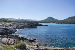 People enjoy a sunny day at Cala Agulla in Mallorca, Spain Stock Photo
