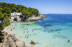 People enjoy a sunny day at Cala Gat in Mallorca, Spain. People enjoy a sunny day on a beach in Cala Gat in Mallorca, Spain Stock Images