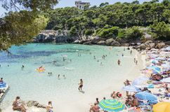 People enjoy a sunny day at Cala Gat in Mallorca, Spain. July 2016, Mallorca, Spain. People enjoy a sunny day on a beach in Cala Gat Stock Images