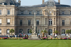 People enjoy sunny day in the Luxembourg Garden in Paris. Luxembourg Palace is the official residence of the French Senate royalty free stock photos