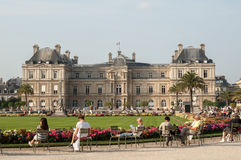 People enjoy sunny day in the Luxembourg Garden in Paris. Luxembourg Palace is the official residence of the French Senate stock image