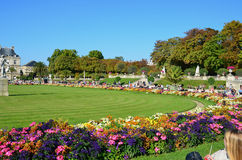 People enjoy sunny day in the Luxembourg Garden in Paris. Luxembourg Palace is the official residence of the French Senate royalty free stock photo