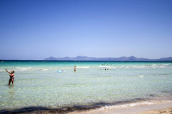 People enjoy a sunny day at Playa del Muro in Mallorca, Spain Stock Images