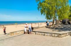 People enjoy the sunny spring day on the Baltic sea gulf beach in Jurmala resort, Latvia. Royalty Free Stock Image