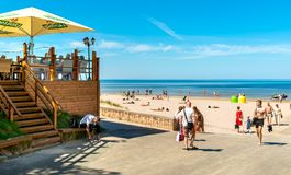 People enjoy the sunny spring day on the Baltic sea gulf beach in the Maiori resort, Jurmala. Royalty Free Stock Photography